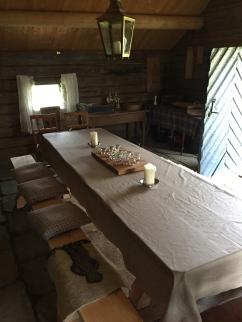Pledd, sauskinn og puter benyttes. Småbord i bakgrunnen kan brukes til oppdekking av mat.